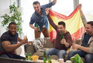 Group of men watching sporting event on television holding Spanish flag celebratingの写真素材 [FYI03547184]