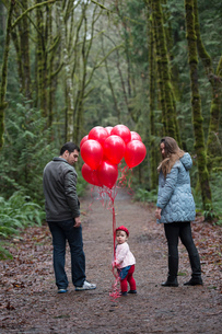 Portrait of female toddler holding a bunch of red balloons with parents in forestの写真素材 [FYI03547295]