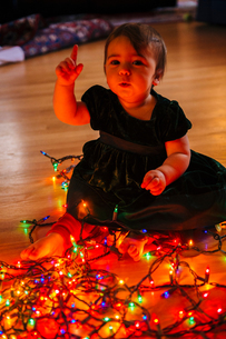Female toddler raising hand whilst playing with multi-coloured christmas lights on floorの写真素材 [FYI03547298]