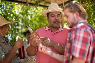 Market trader selling bottle of liquor to touristの写真素材 [FYI03547406]