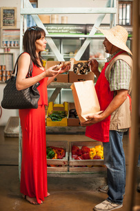 Market trader selling mushrooms to womanの写真素材 [FYI03547455]