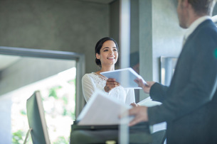 Office worker handing paperwork to businessman at office deskの写真素材 [FYI03547493]