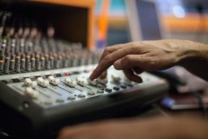 Woman using mixer desk in recording studio, focus on handの写真素材 [FYI03547564]