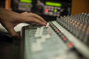 Woman using mixer desk in recording studio, focus on handの写真素材 [FYI03547565]