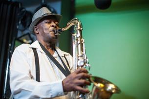 Male musician in recording studio, playing saxophoneの写真素材 [FYI03547571]