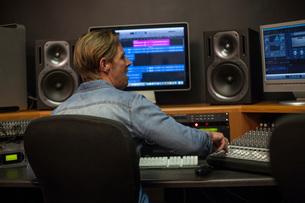 Man using mixer desk in recording studio, rear viewの写真素材 [FYI03547584]