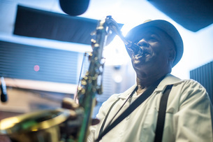 Male musician in recording studio, playing saxophoneの写真素材 [FYI03547586]