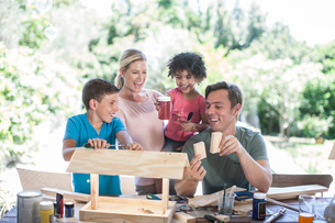 Family doing crafts together, making birdhouseの写真素材 [FYI03547617]