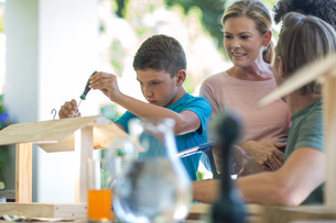 Family doing crafts together, making birdhouseの写真素材 [FYI03547618]