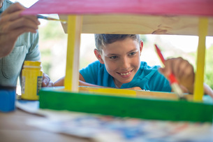 Father and son doing crafts together, painting wooden birdhouseの写真素材 [FYI03547623]