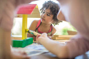 Family doing crafts together, painting wooden birdhouseの写真素材 [FYI03547624]