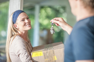 Moving house: woman carrying cardboard box, man holding house keysの写真素材 [FYI03547679]