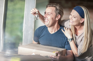 Moving house: man holding cardboard box, woman holding house keys in front of his faceの写真素材 [FYI03547680]