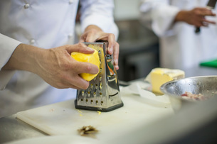 Chef grating cheese in kitchenの写真素材 [FYI03547717]