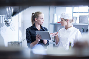Waitress and chef discussing orders on digital tablet in kitchenの写真素材 [FYI03547769]