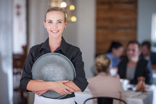 Waitress with serving tray in busy restaurantの写真素材 [FYI03547774]