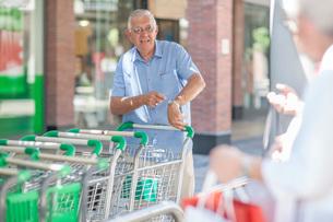 Senior man at supermarket, returning shopping trolleyの写真素材 [FYI03547879]