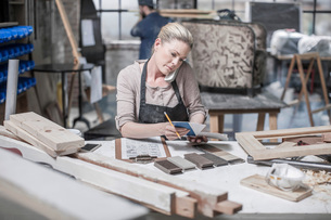 Craftswoman talking on smartphone and checking diary in antique restoration workshopの写真素材 [FYI03547924]