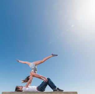 Couple practising partner yoga on benchの写真素材 [FYI03548007]