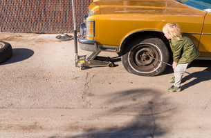 Boy removing wheel nuts from flat tyreの写真素材 [FYI03548027]