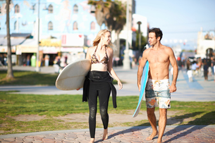 Surfing couple carrying surfboards at Venice Beach, California, USAの写真素材 [FYI03548065]