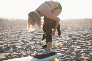 Young female surfer putting on wetsuit on Venice Beach, California, USAの写真素材 [FYI03548067]