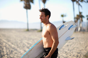 Male surfer carrying surfboard on Venice Beach, California, USAの写真素材 [FYI03548071]