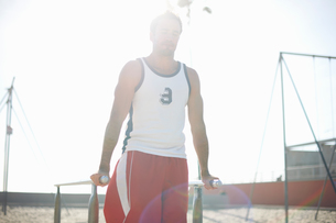 Mid adult man exercising on beach, using gymnastics parallel barsの写真素材 [FYI03548126]