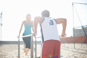 Couple exercising on beach, using gymnastics parallel barsの写真素材 [FYI03548127]