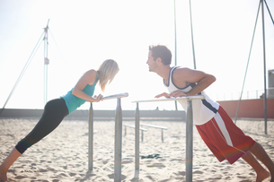 Couple exercising on beach, stretching, using gymnastics parallel barsの写真素材 [FYI03548129]