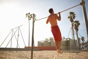 Mid adult man exercising on beach, using gymnastics training bar, rear viewの写真素材 [FYI03548131]