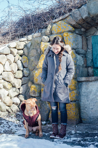 Full length view of woman with dog in front of dry stone buildingの写真素材 [FYI03548243]