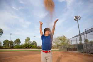 Boy throwing baseball glove mid air at baseball practiseの写真素材 [FYI03548274]