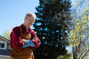 Senior man wearing carpenters apron in gardenの写真素材 [FYI03548421]