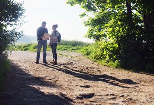 Couple hiking on dirt track reading mapの写真素材 [FYI03548466]