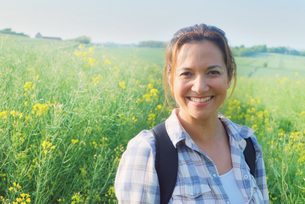 Portrait of woman in rapeseed field looking at camera smilingの写真素材 [FYI03548469]
