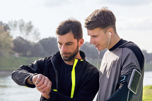 Two male friends outdoors, ready to work out, looking at activity trackerの写真素材 [FYI03548498]