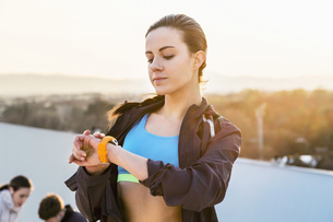 Young woman, outdoors, looking at activity trackerの写真素材 [FYI03548517]