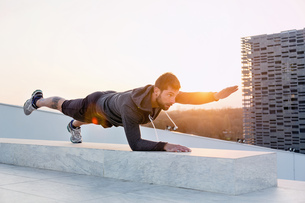 Mid adult man exercising outdoors, in yoga positionの写真素材 [FYI03548521]
