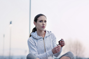 Young woman, wearing sports clothing, putting on activity trackerの写真素材 [FYI03548537]
