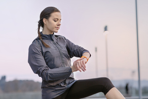 Young woman, wearing sports clothing, looking at activity trackerの写真素材 [FYI03548538]