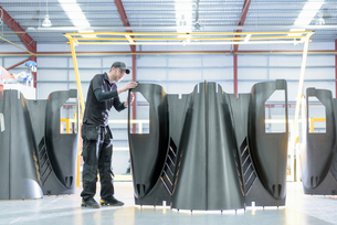 Engineer inspecting carbon fibre body parts in racing car factoryの写真素材 [FYI03548684]