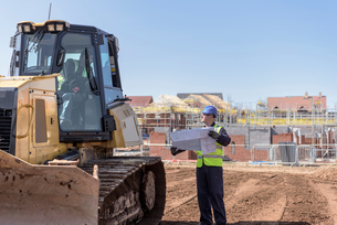 Builder with site plans in discussion with bulldozer driver on housing building siteの写真素材 [FYI03548731]
