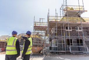 Builders discussing housing development on building siteの写真素材 [FYI03548739]