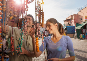 Young couple at market looking at beads, Jemaa el-Fnaa Square, Marrakesh, Moroccoの写真素材 [FYI03548864]