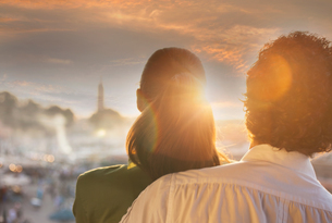 Rear view of couple looking at sunset over Jemaa el-Fnaa Square at sunset, Marrakesh, Moroccoの写真素材 [FYI03548867]
