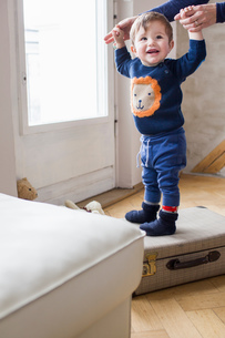 Baby boy holding mothers hands and standing on suitcaseの写真素材 [FYI03548954]