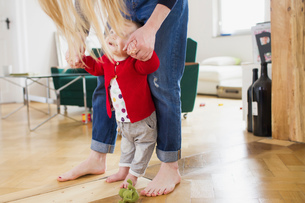 Baby girl holding mothers hands to take first stepsの写真素材 [FYI03548960]