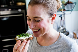 Mid adult woman eating rye bread snack in kitchenの写真素材 [FYI03549037]