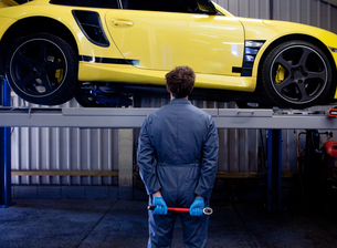 Male mechanic checking yellow sports car, holding socket wrench behind his back, rear viewの写真素材 [FYI03549060]